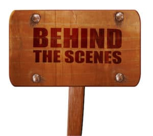 behind the scenes text on wooden sign