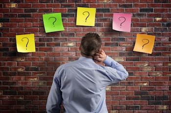 businessman thinking with question marks written on adhesive notes stuck to a brick wall