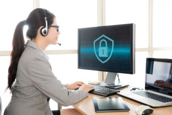 professional pretty female office worker wearing headset talking with customer and typing data into online system to solve cyber security problem.